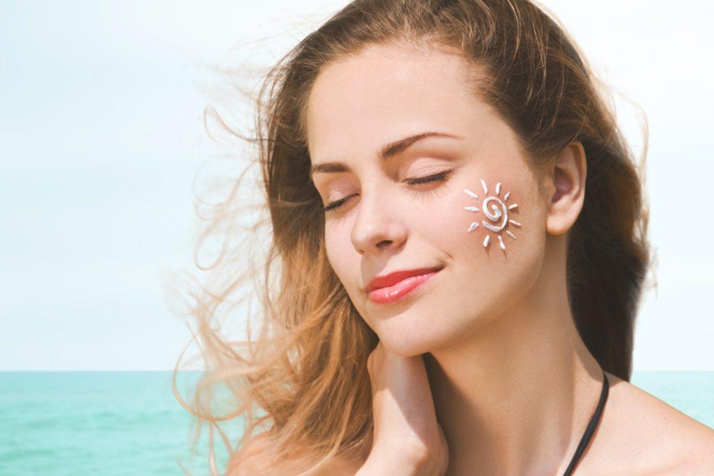 Sunscreen. Suntan Lotion Woman Applying Sunscreen Solar Cream. Beautiful happy cute Girl applying Sun Tan Cream on her Face over ocean background. Sun Tanning. Skin care and Protection. Vacation